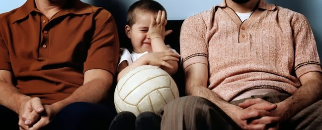Boy (3-5) with football sitting between two men on sofa