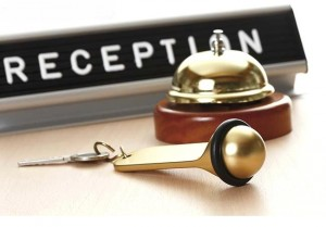 Reception sign with service bell and hotel key on desk
