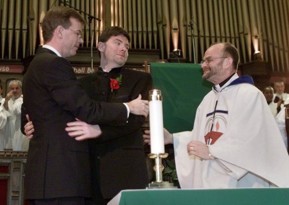 GAY COUPLE EMBRACE DURING WEDDING CEREMONY IN TORONTO CHURCH