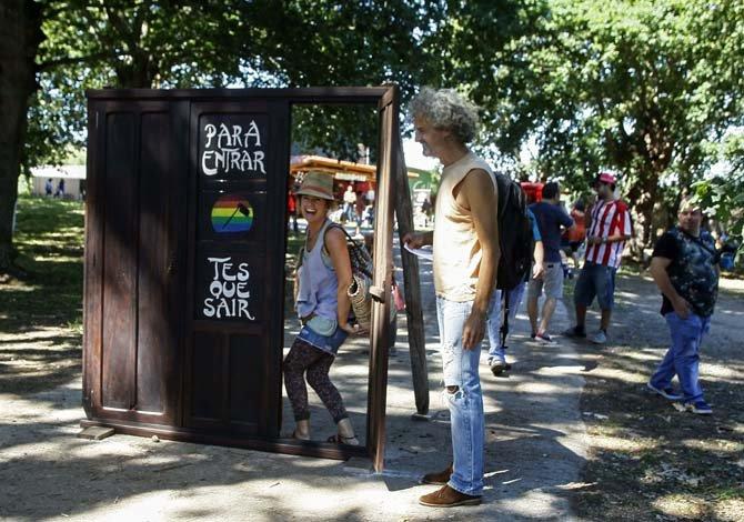 GRA122. MONTERROSO (LUGO), 29/08/2015.-En la granja de Maruxa en Monterroso se celebra la segunda fiesta gay, con el nombre de SON AGROGAY. En la imagen una chica entra en la puerta de un armario, instalado en la entrada de la finca. Gays y Lesbianas se dan cita en este entorno rural.-EFE/ELISEO TRIGO