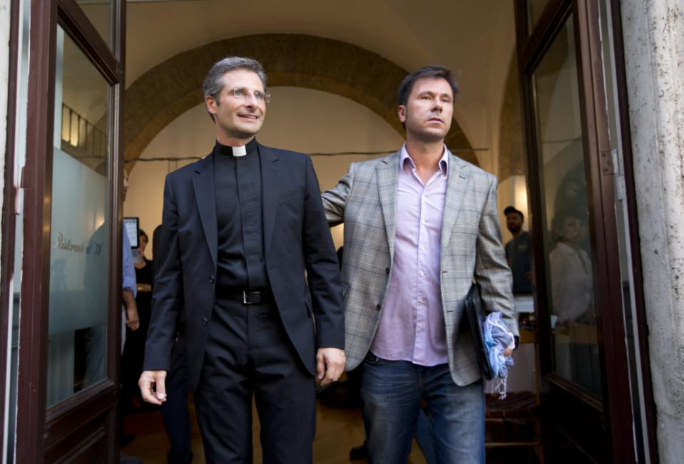 Monsignor Krzysztof Charamsa, left, and his boyfriend Eduard, surname not given, pose for a photo as they leave a restaurant after a press conference in downtown Rome, Saturday Oct. 3, 2015. Vatican on Saturday fired a monsignor who came out as gay on the eve of a big meeting of the world's bishops to discuss church outreach to gays, divorcees and more traditional Catholic families. (AP Photo/Alessandra Tarantino)