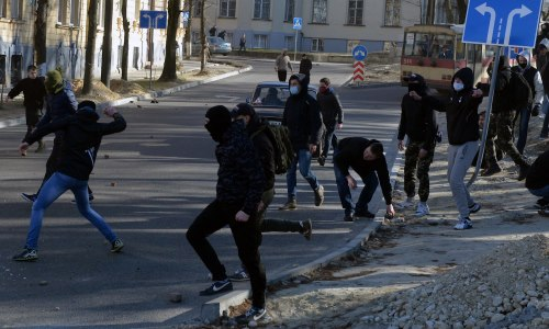 Masked right-wing militants throw rocks during an attack against gay people on March 19, 2016 in Lviv. Some 200 right-wing militants on March 19, 2016 attacked dozens of gay people with smoke bombs and stones in Lviv, a nationalist bastion in western Ukraine, an AFP journalist witnessed. The attack occurred as representatives of the lesbian, gay, bisexual and transgender (LGBT) community left a Lviv hotel which is hosting a gay rights event this weekend. / AFP / YURIY DYACHYSHYN (Photo credit should read YURIY DYACHYSHYN/AFP/Getty Images)