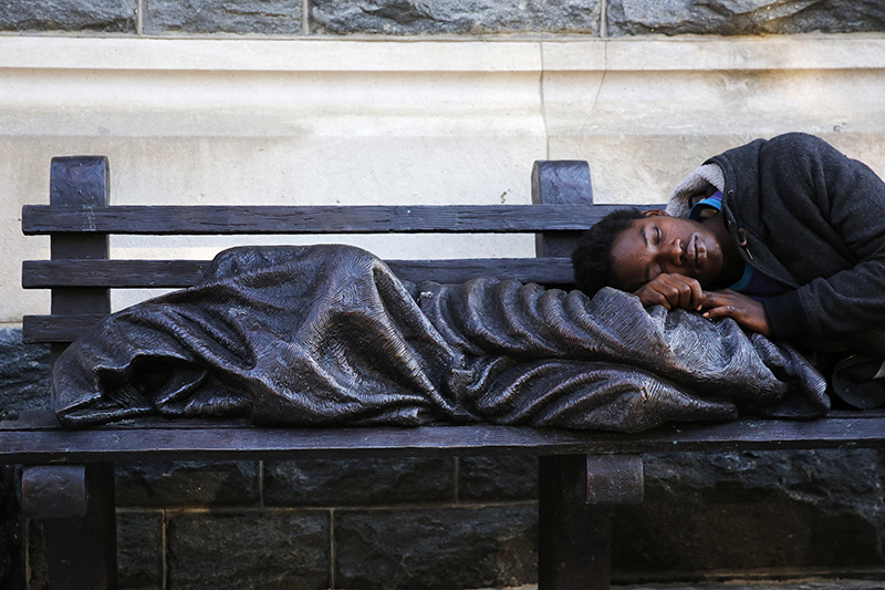 A man sleeps on a sculpture of a figure called 'Homeless Jesus' in front of the Archdiocese of Washington Catholic Charities offices in Washington, on September 16, 2015. Photo courtesy of REUTERS/Jonathan Ernst *Editors: This photo may only be republished with RNS-POPE-HOMELESS, originally transmitted on Sept. 24, 2015.