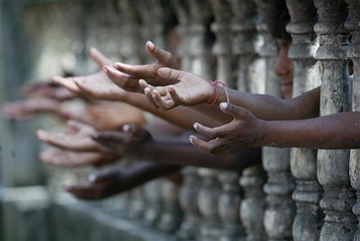 Homeless children reach out from behind a fence as they wait to collect free clothes at a local charity in the northeastern Indian city of Siliguri September 27, 2006. REUTERS/Rupak De Chowdhuri (INDIA) BEST QUALITY AVAILABLE