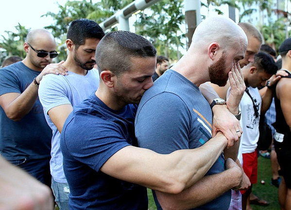 Caleb McGrew, 36, right, wipes tears as he stands with his partner Yosniel Delgado Giniebra, 37, center, during a vigil in memory of the victims of the Orlando mass shooting, Sunday, June 12, 2016, in Miami Beach, Fla.A gunman opened fire inside a crowded gay nightclub early Sunday, before dying in a gunfight with SWAT officers, police said. (AP Photo/Lynne Sladky)