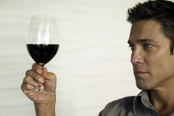 Man looking at glass of red wine