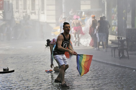 A participant in the Gay Pride event in support of Lesbian, Gay, Bisexual and Transsexual (LGBT) rights reacts as others flee after Turkish police use a water canon to disperse them in Istanbul, Turkey, Sunday, June 28, 2015. Turkish police have used water cannons and tear gas to clear gay pride demonstrators from Istanbul's central square. Between 100 and 200 protestors were chased away from Taksim Square on Sunday after a police vehicle fired several jets of water to disperse the crowd. It wasn't immediately clear why the police intervened to push the peaceful if noisy protest away from the area. (AP Photo/Emrah Gurel)