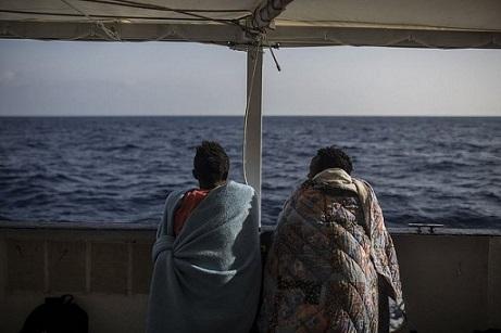 dos-migrantes-hablan-y-observan-el-mar-desde-el-open-arms