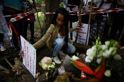 People lay white roses and light candles at the site where Vanesa Campos, a 36 year-old transsexual sex worker was killed the week before, at the Bois de Boulogne in Paris, on August 24, 2018. / AFP / Lionel BONAVENTURE