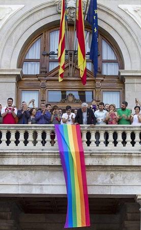 Valencia (Comunidad Valenciana), 26/06/2015. El alcalde de Valencia, Joan Ribó (centro), despliega, esta tarde, desde el balcón del Ayuntamiento la bandera arco iris con motivo del Día Internacional del Orgullo Lésbico, Gay, Transexual y Bisexual. EFE/Manuel Bruque.
