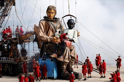 Puppeteers pulls cords as they animate giant puppets of a boy and a deep-sea diver as they are paraded through the streets of Le Havre, northwestern France, on July 7, 2017, during a performance by French mechanical marionette street theatre company Royal de Luxe. / AFP PHOTO / CHARLY TRIBALLEAU