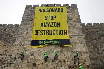 Greenpeace activists hang a large banner on the ramparts of the Old City of Jerusalem with a message to the visiting Brazilian president concerning the Amazon, on April 1, 2019. - Brazilian President Bolsonaro is on a four-day official visit to Israel. (Photo by Ohad ZWIGENBERG / AFP) / Israel OUT / ISRAEL OUT / The erroneous mention appearing in the metadata of this photo by Ohad Zwwingenberg has been modified in AFP systems in the following manner: correcting byline from Ohad ZWWIGENBERG to Ohad ZWIGENBERG and adding restrictions . Please immediately remove the erroneous mention from all your online services and delete it from your servers. If you have been authorized by AFP to distribute it to third parties, please ensure that the same actions are carried out by them. Failure to promptly comply with these instructions will entail liability on your part for any continued or post notification usage. Therefore we thank you very much for all your attention and prompt action. We are sorry for the inconvenience this notification may cause and remain at your disposal for any further information you may require. (Photo credit should read OHAD ZWIGENBERG/AFP/Getty Images)