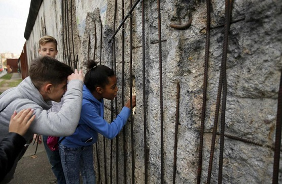 children-look-through-a-hole-of-the-former-berlin-wall-border-at-the-memorial-site-in-bernauer-strasse-in-berlin
