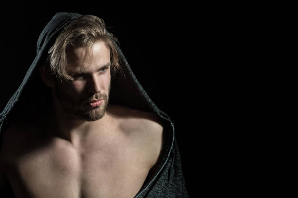 Stylish sexy man with muscular torso wearing hoodie. Muscle athletic man with hood, abdominal on black isolated background. Naked guy in the hood