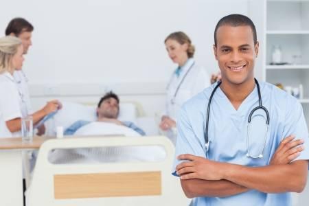 20501122-doctor-atractivo-con-los-brazos-cruzados-de-pie-en-frente-de-equipo-médico-atendiendo-a-un-paciente