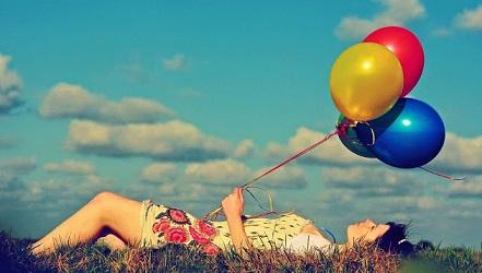 chica-tumbada-en-la-hierba-con-globos