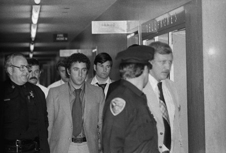 "(Original Caption) Dan White (directly beneath ""Fraud"" sign) suspect in the killing of San Francisco Mayor George Moscone & Supervisor Harvey Milk is led by police officers towards jail elevator at Hall of Justice here. White recently resigned as a member of the Board of Supervisors, but later said he wanted his job back. Moscone had called a news conference to announce that he would not reappoint White."