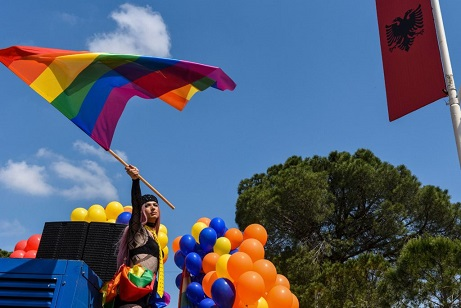 An Albanian LGBT activist waves a rainbow flag as she attends Tirana Gay Pride to mark the International Day Against Homophobia and Transphobia (IDAHOT) on the main boulevard in Tirana on May 13, 2018. - Only in recent years has the LGBT community in Albania emerged from marginalized and underground activities to hold public events and parades, although not entirely without causing controversy and prejudice in this small Balkan nation which until the collapse of the communist regime in 1990 penalized homosexuality. (Photo by Gent SHKULLAKU / AFP) (Photo credit should read GENT SHKULLAKU/AFP via Getty Images)