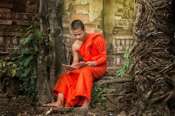 monje-leyendo-libro-budista-fuera-antiguo-templo_28717-143