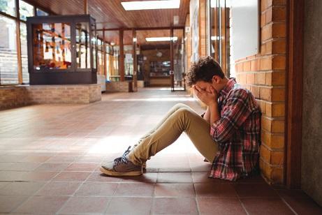 sad-schoolboy-sitting-alone-in-corridor-59JRNLV-1-1024x683