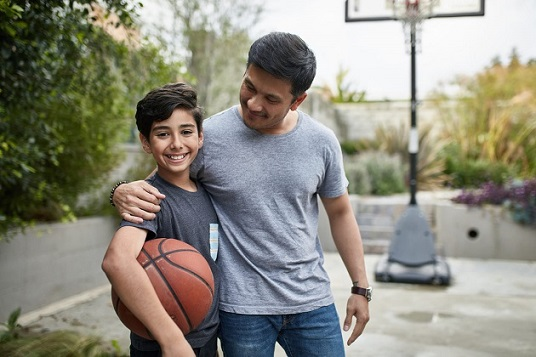 Portrait of happy boy standing with father at basketball court. Mid adult man and child are smiling in backyard. They are in casuals during weekend.