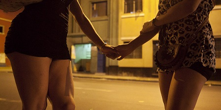 Danuska, left, holds hand with her friend as she passes by on her way to work.
