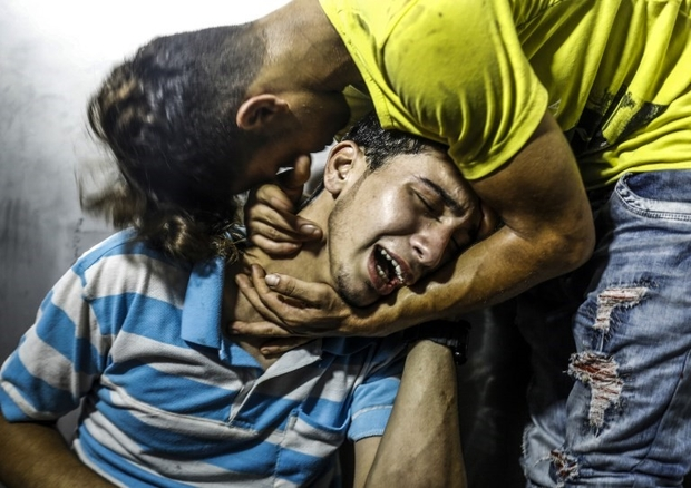 Palestinian youths mourn at al-Shifa hospital morgue on July 14, 2018 after two teenagers were killed in one of a series of Israeli raids. Aged 15 and 16, two Palestinians were on a road west of Gaza City when an air strike struck a nearby empty building, the enclave's health ministry said. Israel unleashed a wave of strikes against Gaza on July 14, while scores of rockets were fired back across the border from the territory. / AFP PHOTO / ANAS BABA