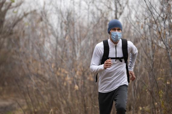hombre-mascarilla-bosque-corriendo_23-2148776298