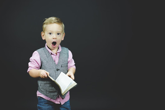 A closeup shot of a surprised child holding the bible with a black background