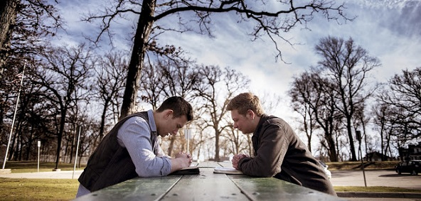Two men sitting on a bench with bibles and praying in a garden under sunlight with a blurry background